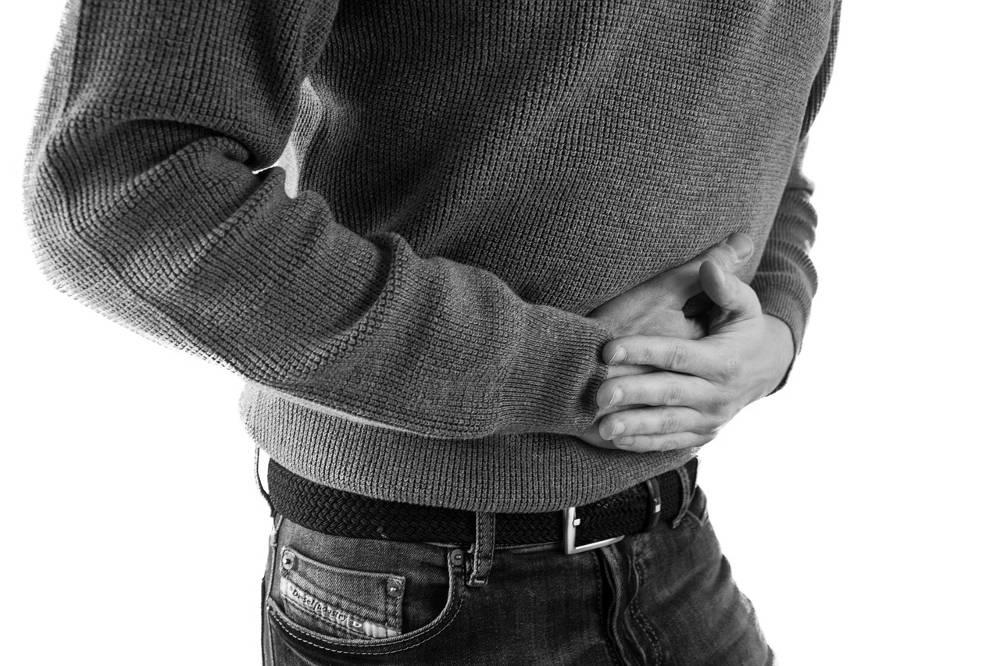 Bild mit sich bauchhaltendem Mann als Symbol für Krankheiten als Folgen von Spielsucht