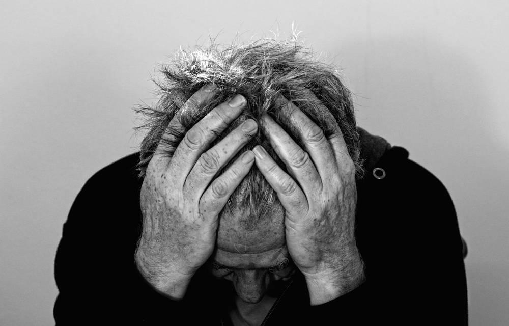 Mann der seinen Kopf in Händen vergräbt vor dem Spielsucht bekämpfen