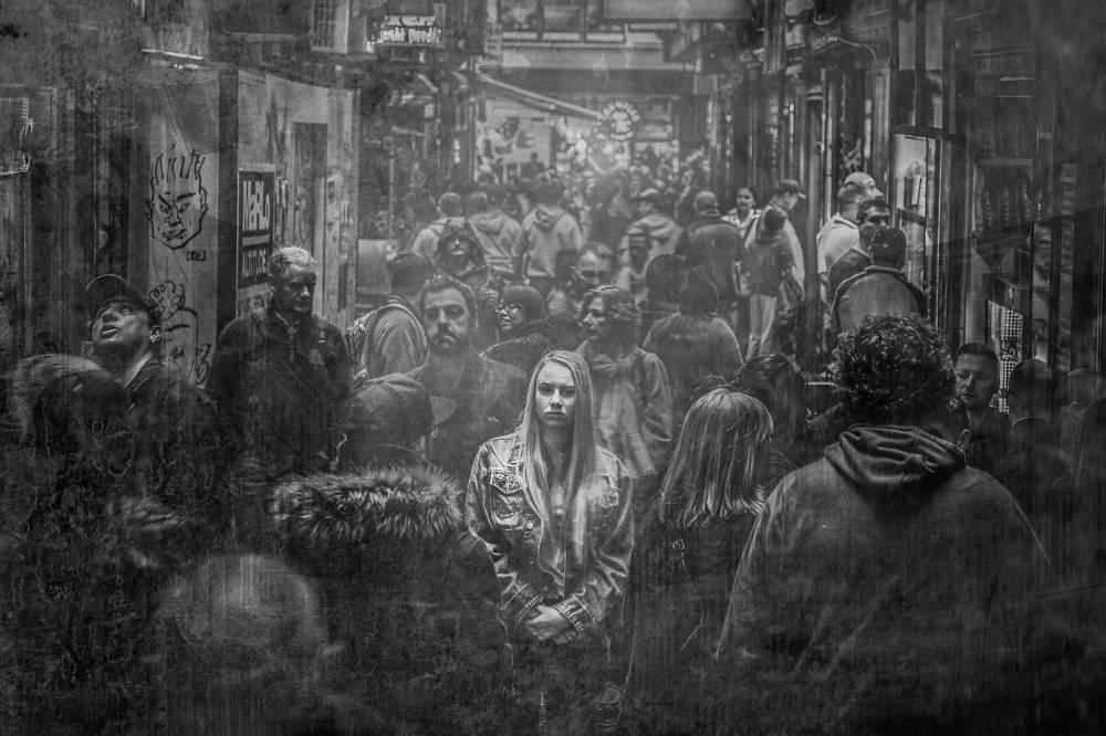 Eine Frau unter vielen Menschen als Symbol für Spielsucht Einsamkeit und Liebesverlust