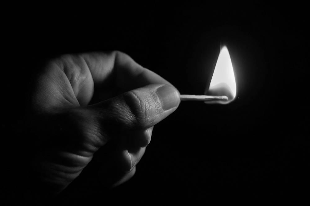 Mann das brennende Streichholz hält als Symbol für Spielsucht Hilfe